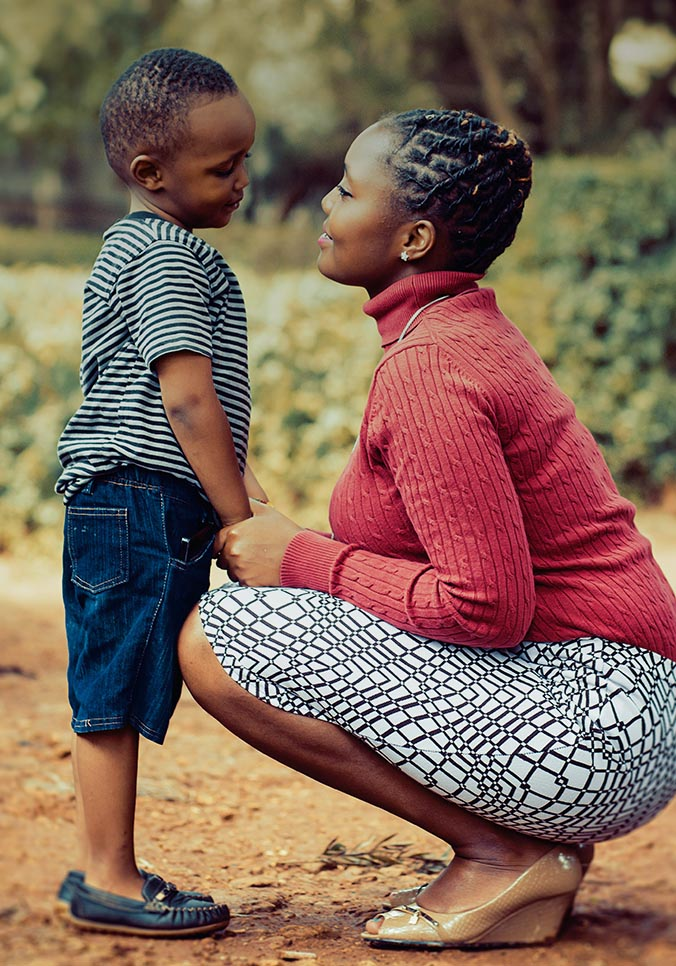A loving mother and her son face each other and smile at Metro Community Development.