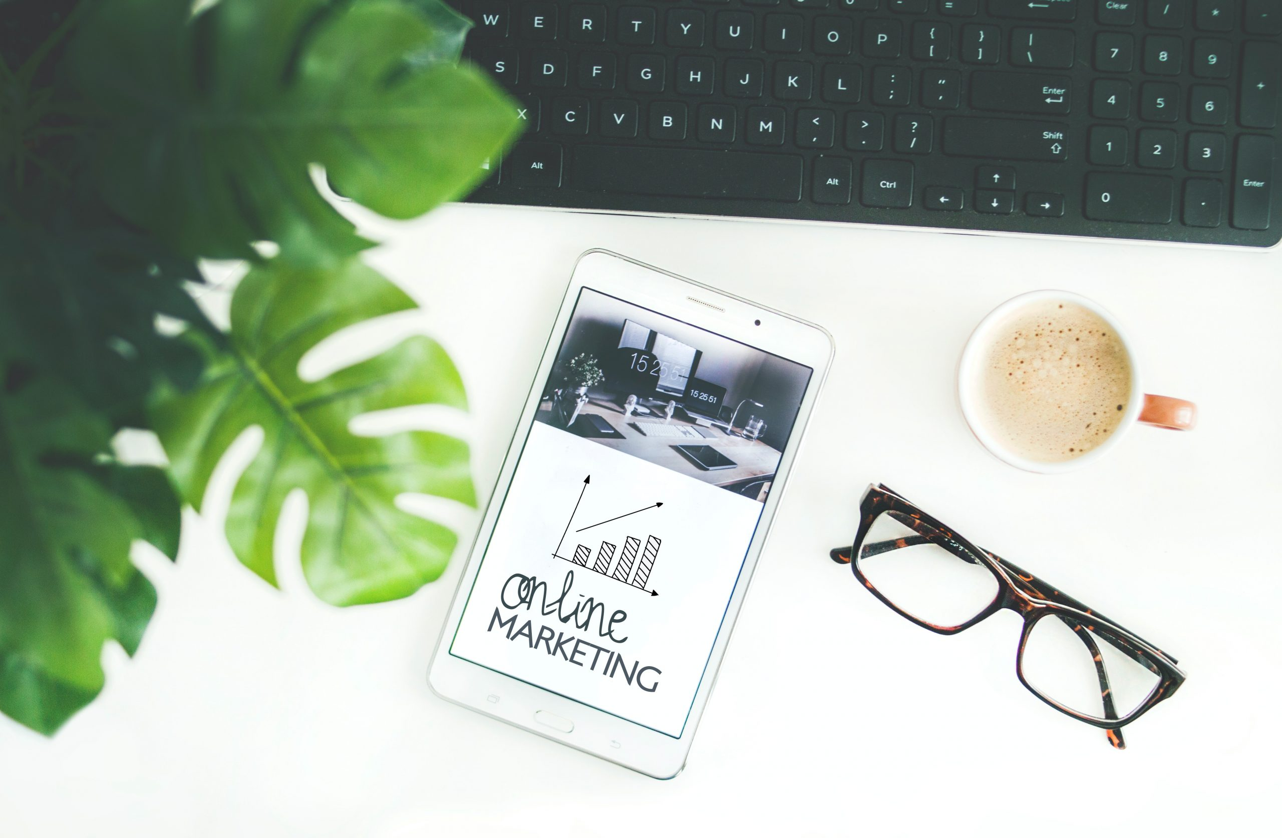 Digital Marketing Strategy - A clean desktop featuring a monstera plant, a tablet, a pair of reading glasses, a cup of coffee, and a desktop keyboard.