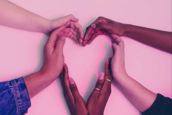 6 Heart Health Tips From a Cardiologist - A group of people join their hands together to form a heart shape.